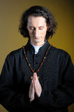 Praying priest with wooden cross Royalty Free Stock Photos
