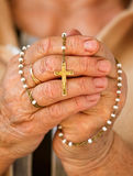 Praying with a rosary Stock Photo