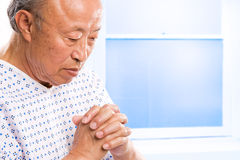 Praying senior asian in hospital stock photo
