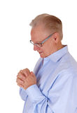 Praying senior man with folded hands. Royalty Free Stock Image