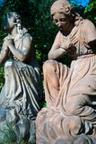 Praying statues. Two kneed women: the first is joigning hands over her chest, the second is joinging hands for prayer. Ones arm part is missing Royalty Free Stock Images