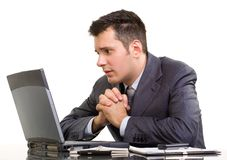Praying stock broker. Young Caucasian man in suit, praying and looking at a laptop Stock Images