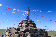 Praying stone and prayer flags Royalty Free Stock Image