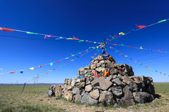 Praying stone and prayer flags on steppe Stock Image