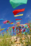 Praying stone and prayer flags on steppe Stock Photos