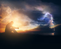 Praying through the storm. A man is praying through the sunrise and the storm Royalty Free Stock Photos