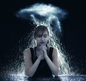 Praying in the storm. A woman is being soaked by a storm and still prays Stock Photo