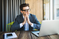 Praying for success. Front view of thoughtful young man holding hands on chin and looking at the laptop while sitting at his worki Royalty Free Stock Photos