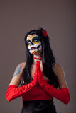 Praying Sugar skull girl. In red evening dress and gloves royalty free stock photos