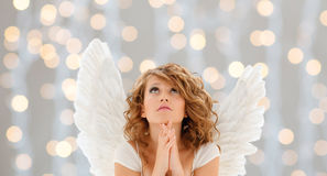 Praying teenage angel girl or young woman. Religion, faith, christmas, holidays and people concept - praying teenage girl or young woman with angel wings over royalty free stock image