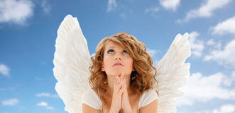 Praying teenage angel girl or young woman. Religion, faith, holidays and people concept - praying teenage girl or young woman with angel wings over blue sky and royalty free stock image