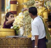Praying to Buddha. A Burmese man and woman pour water over a statue of Buddha after placing flowers around Buddha's neck in prayer at Shwedagon Paya, Yangon Royalty Free Stock Images