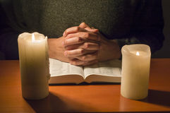 Praying to the candlelight. Man praying with a bible in the candlelight royalty free stock photos