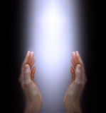 Praying to the Divine Spirit. Female hands reaching up with shaft of white light streaming down Stock Image