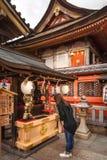 Praying to the god of love at Kiyomizu-dera in Kyoto. Kyoto, Japan -November 2, 2018: Young girl praying in front of Jinja-Jishu shrine at the famous Kiyomizu royalty free stock image