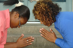 Praying together. A picture of a mother and daughter praying together Royalty Free Stock Image