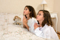 Praying vintage girls. Adorable victorian girls kneeling in their vintage bedroom and praying Royalty Free Stock Photo