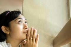 Praying woman. Asian young woman praying by the window in the church Stock Photo