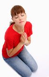 Praying woman. A woman praying to God with closed eyes isolated on a white background Stock Photo