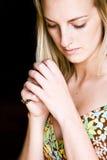 Praying woman. Blond praying woman against black background Stock Photos