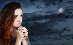 Praying woman against cloudy sky with moon Royalty Free Stock Photo