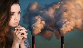 Praying woman against of pipes polluting an atmosphere Royalty Free Stock Photo