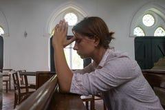 Praying woman in christian church praying God for help stock image