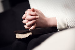 Praying woman folding hands over bible Stock Photo