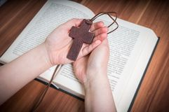 Praying woman holds brown cross. Bible in background Stock Photo