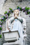 Praying Woman Marble Sculpture at Flowers Garland. Closeup marble sculpture of praying woman against stone and violet flowers garland Stock Photography