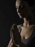 Praying woman. Prayer close up portrait, black bac Stock Photo