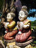 Praying Women Statue. Two colored statues of kneeling praying women in Thailand Stock Photography