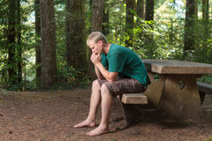 Praying in the woods. Young man sitting at a picnic table in the woods praying Royalty Free Stock Photo
