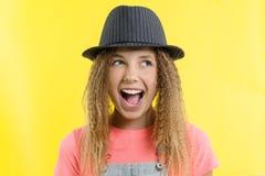 Prazer, felicidade, alegria, vitória, sucesso e sorte Menina adolescente em um fundo amarelo fotografia de stock