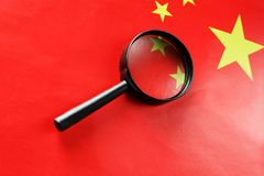 The PRC flag is looked through a magnifying glass. Spies and sightings of the People s Republic of China. Monitoring the status of. The People`s Republic of stock photography