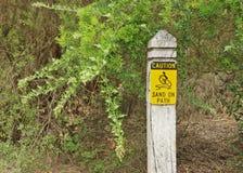 Précaution-sable noir et jaune sur le signe de chemin Photos stock