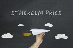 Preço e mão de Ethereum com avião de papel fotos de stock