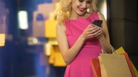 Preços de verificação shopaholic fêmeas de suas compras em lojas em linha, app móvel video estoque