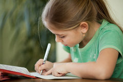 Pre-adolescent girl concentrates on her studies. Girl does homework in her copybook Stock Photos