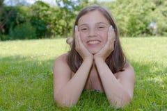 Pre adolescente hermoso que pone en hierba Imagen de archivo libre de regalías