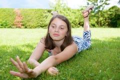 Pre adolescente hermoso que pone en hierba Imagen de archivo