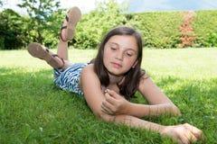 Pre adolescente hermoso que pone en hierba Imágenes de archivo libres de regalías