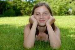 Pre adolescente hermoso que pone en hierba Fotos de archivo libres de regalías