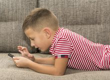 Pre-adolescente que juega con el smartphone puesto en el sofá Fotografía de archivo libre de regalías