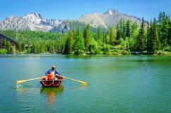 Père avec l'aviron d'enfant dans le bateau de palette Photo libre de droits