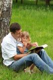 Père avec le descendant de chéri affichant la bible Photos stock