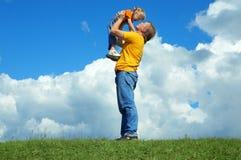 Père avec le descendant sur l'herbe verte Image libre de droits