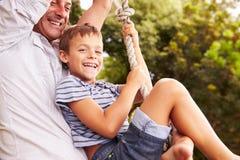 Père balançant avec le fils à un terrain de jeu Image stock