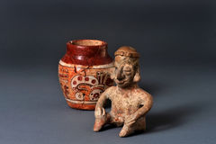 Pre-Columbian Art. Mayan seated man and painted clay jar Stock Images