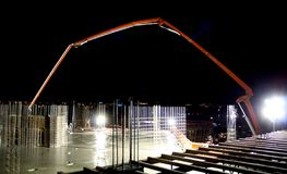 Pre-Dawn Concrete Pour. An articulated-boom concrete pump feeds cement to an upper deck on a multistory commercial construction project; Stands of rebar indicate stock images